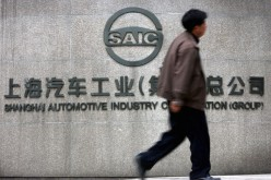 A Chinese man walks past the office building of Shanghai Automotive Industry Corp. (SAIC) on April 12, 2005, in Shanghai, China.