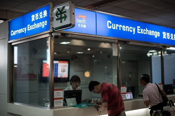 A man changes foreign currency into Chinese yuan at a currency exchange office at Hongqiao airport in Shanghai.