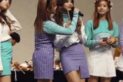 TWICE members, including Tzuyu, on stage during the fan meeting.