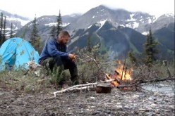 A man sits in front of a bonefire while being one with nature.