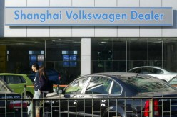 A couple walk through a Volkswagen auto dealership in Beijing.