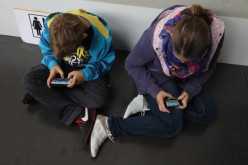 Children play video games on smartphones while attending a public event