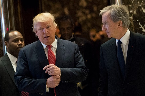 L to R) President-elect Donald Trump and French businessman Bernard Arnault, chief executive officer of LVMH, emerge from the elevators to speak to reporters at Trump Tower, Jan. 9, 2017, in NY.