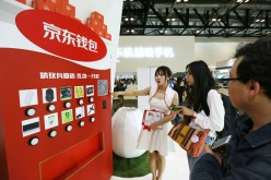 A conference participant visits one of the product booths during a GMIC event in Bejing.
