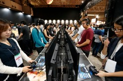 Visitors play a video game on Sony Interactive Entertainment Inc. PlayStation 4 game consoles the Bandai Namco Holdings Inc. booth at the Tokyo Game Show 2016 on September 15, 2016 in Chiba, Japan.