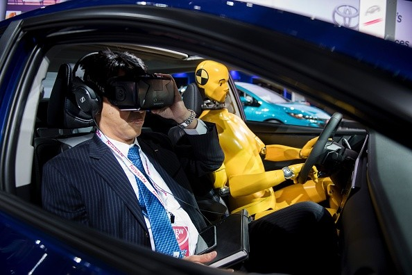 A reporter uses an Oculus Rift virtual reality headset during a Toyota safety demonstration at the 2017 North American International Auto Show.