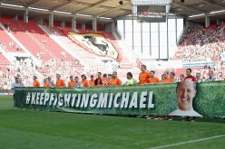 Both teams hold up a banner that reads 'Keep fighting Michael' prior to the 'Champions for charity' football match between Nowitzki All Stars and Nazionale Piloti in honor of Michael Schumacher at Opel Arena on July 27, 2016 in Mainz, Germany.