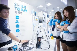 Twin girls pay by facial recognition on the computer at the Ant Financial booth during the 2016 Computing Conference at Yunqi Cloud Town in Hangzhou.