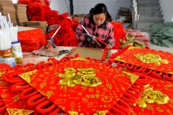 A woman makes a Chinese knot for a wall decoration at Liujing village, Xiayi township in Central China's Henan Province, Dec 3, 2016.