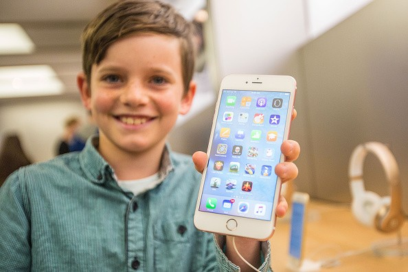 Levi aged 10, shows of the new iPhone 6s Plus in rose gold as crowds wait in anticipation for the release of the iPhone 6s and 6s Plus.