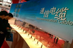 Visitors look at telecommunications cables displayed at an exhibition in Beijing.