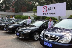 Drivers stand by cars of Shouqi Limousine & Chauffeur, a taxi-booking service, on Sept. 16, 2015, in Beijing, China.