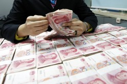 A Chinese clerk counts renminbi yuan banknotes at a bank in Huaibei, Anhui Province.
