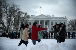 Chinese tourists from Beijing participate in a snowball fight in front of the White House, Feb. 17, 2015, in Washington, DC.