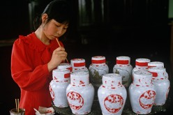 A woman handpaints jars of rice wine in a rice wine factory in Shaoxing.