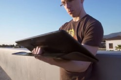 A user is checking his massive tablet for updates while situated outdoors.