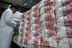 An employee counts 100 yuan banknotes at the Korea Exchange Bank headquarters in Seoul.
