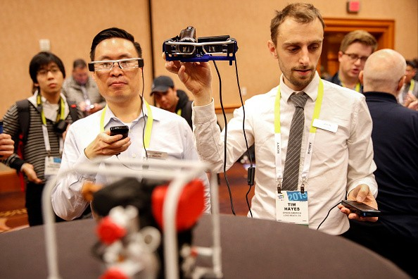 Barry Po, director of product management at Ngrain Canada Corp., and Tim Hayes, software engineer at Ngrain Canada Corp., control Epson BT-200 augmented reality headsets.