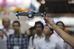 Visitors look at a demonstration of the SZ DJI Technology Co. DJI Mavic Pro drone in the SZ DJI booth at the Combined Exhibition of Advanced Technologies (CEATEC) show.