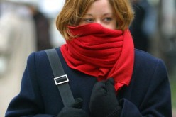 A woman with her scarf wrapped around her nose and mouth, feeling cold