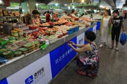 A woman scans the QR code by cellphone to pay for her purchases at a market in Wenzhou, east China's Zhejiang Province.