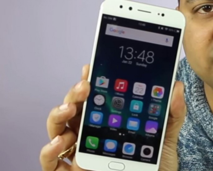 Vivo smartphone is held by hand to display its app features.