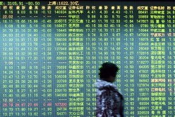 An investor walks past a screen showing stock market movements at a securities firm in Hangzhou.