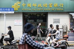 Pedestrians walk past a bank in Shanghai.