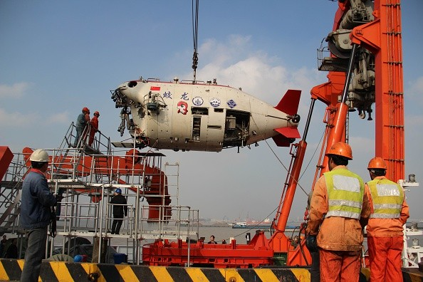 Workers install Jiaolong, China's manned deep-sea research submersible, onto its carrier.