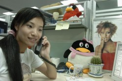 A worker makes a phone call beside an emblem of Tencent QQ instant messaging service, in the headquarters office of the Tencent Holdings Limited in Shenzhen.