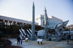 People walk past a display of model missiles including a North Korean Scud-B (C) at the War Memorial of Korea.