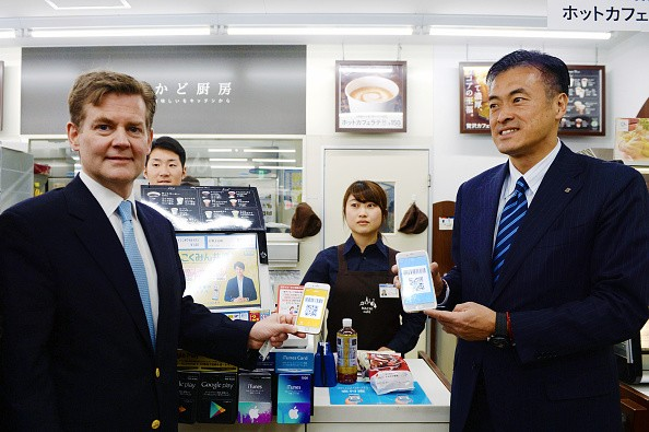 Genichi Tamatsuka (R), CEO of Lawson, and Douglas Feagin (L), senior vice president of Ant Financial Services Group, experience using Alipay at a Lawson convenience store in Tokyo, Japan.