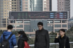 Pedestrians walk past a large screen showing financial data in Shanghai, on Jan. 4, 2017.
