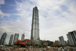 Scrapers scoop ruins at a demolition site of old houses in front of the Jinmao Tower, China's tallest building, on July 5, 2005 in Shanghai, China.