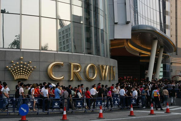 Visitors wait for the casino hotel Crown Macau official opening May 12, 2007 in Macau, China.
