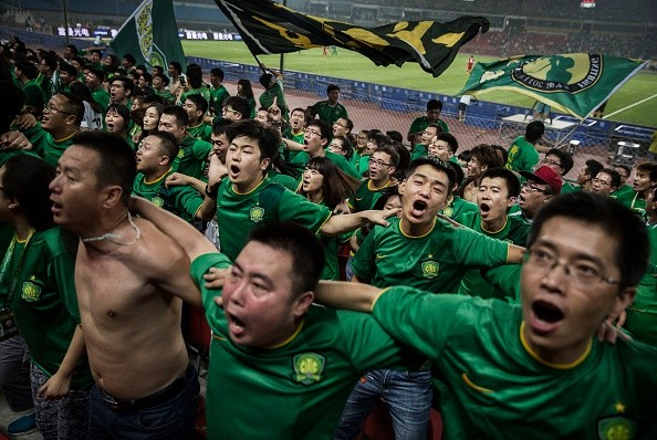 Fans of the Beijing Guoan FC celebrate together after a goal.