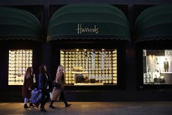 Shoppers walk past Harrods department store.