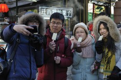 People enjoy popsicle at central street in Harbin City. Rise in consumer spending drives economic growth.