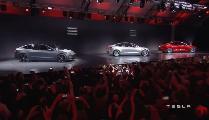 Tesla Model 3 cars are showcased in front a massive crowd.
