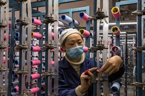 A woman checks threads in a textile factory in Nantong in China's eastern Jiangsu Province.