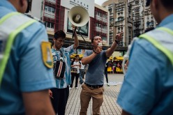 A protester shouts slogans as police stand guard on a street on May 1, 2015 in Macau.