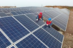 Workers check the grid-connected photovoltaic system built on an abandoned mine at Chihe Town in Chuzhou, Anhui Province.