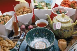 A display of Chinese take-out food and appropriate serving and eating items.