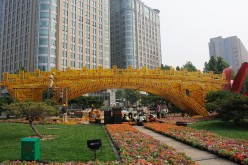 Workers install a golden flower bed called