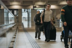 Travelers carrying luggage walk through an airport.