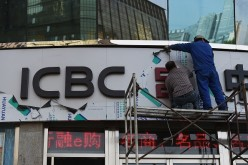 Workers install a sign above the entrance to a branch of the Industrial and Commercial Bank of China.