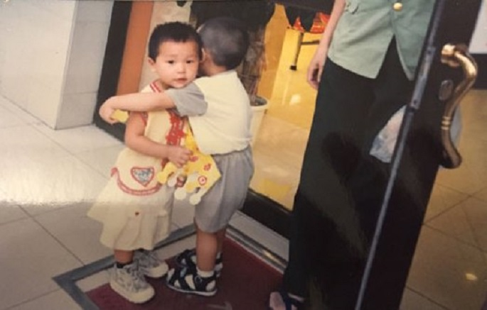 A little boy gives a female kid a hug outside a cake shop in Wanxincun in Hedong District, Tianjin, in Aug. 1999. The grown-up girl now wants to know his identity.