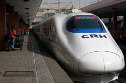 A worker pedals past a CRH (China Railway High-speed) bullet train at Hangzhou Railway Station.