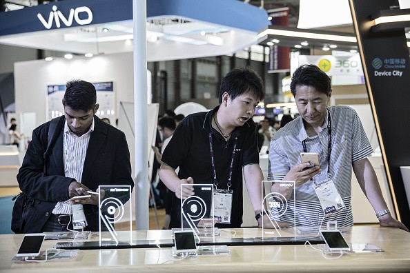 Attendees look at smartphones manufactured by Oppo and Vivo at the Mobile World Congress Shanghai in Shanghai, China.