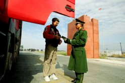 A police officer checks a truck driver's passport at Horgas land port between China and Kazakhstan, Oct. 17, 2005, in Horgas, Xinjiang Uyghur Autonomous Region, China.